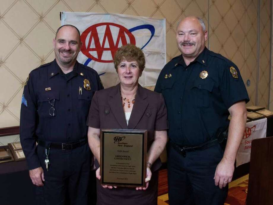 AAA Public Affairs Manager Fran Mayko recently presented Greenwich Police Sgt. John Slusarz and Lt. John Brown with a national Gold Award for the department's comprehensive traffic safety programs. Photo: Contributed Photo