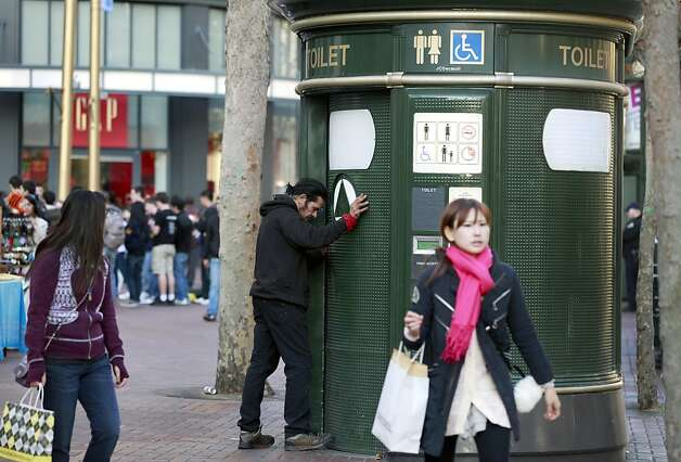 An unidentified man tryês to force open a free automated public toilet on Market Street at Powell that's already occupied by two others. San Francisco's free toilets have been in use since 1995 and have had constant maintenance and sanitary problems. Friday December 9, 2011 Photo: Lance Iversen, The Chronicle