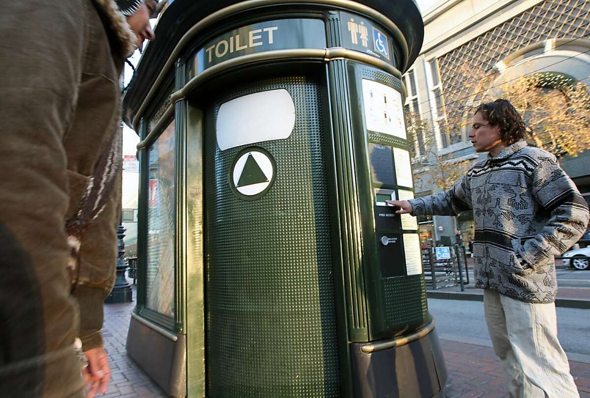 An unidentified man presses the free automated public toilet door button on Market Street at Powell. Two others preventing the door from opening occupied the toilet. San Francisco's free toilets have been in use since 1995 and have had constant maintenance and sanitary problems.