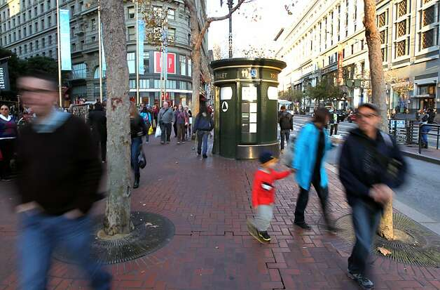 Pedestrians on Market Street at Powell pass a free automated public toilet Friday December 9, 2011. San Francisco's free toilets have been in use since 1995 and have had constant maintenance and sanitary problems. Photo: Lance Iversen, The Chronicle