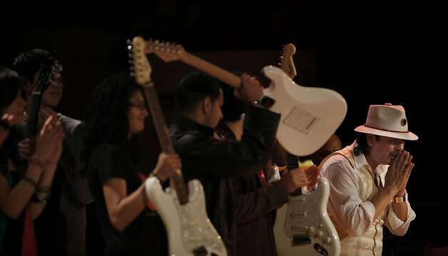 Carlos Santana bows to the crowd in the auditorium after performing at Mission High as students hold up electric guitars donated to the school by Little Kids Rock in San Francisco, Calif. on Monday, October 24, 2011. Photo: Lea Suzuki, The Chronicle