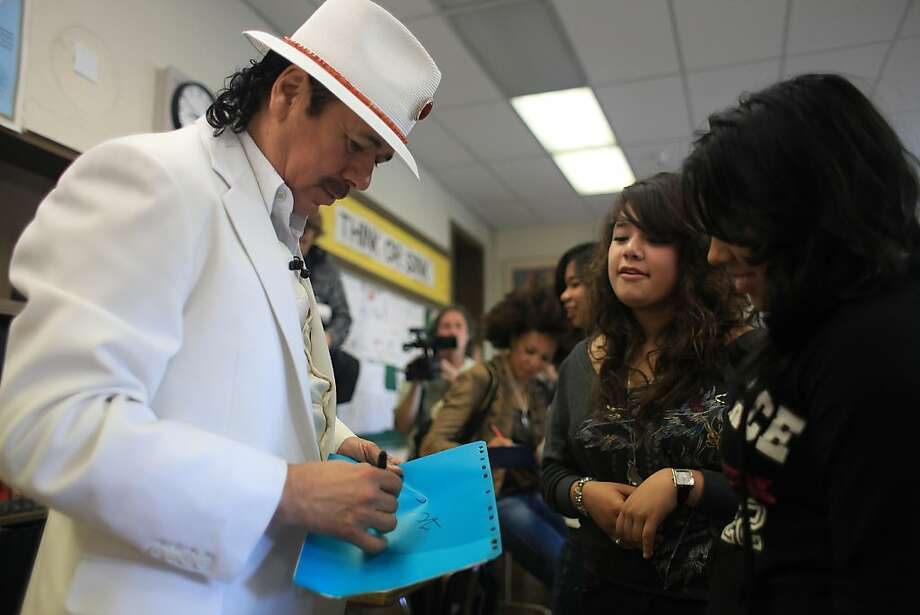 Carlos Santana (left) signs an autograph for Brenda Maya (right) 14, while touring his alma mater Mission High school in San Francisco, Calif. on Monday, October 24, 2011. Photo: Lea Suzuki, The Chronicle