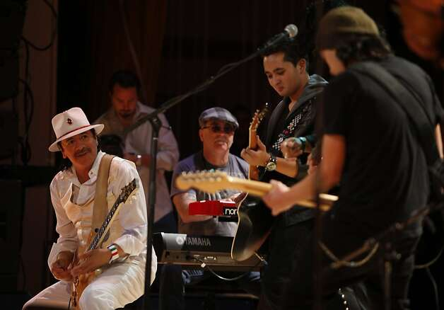 Carlos Santana (left) plays on stage with Mission High graduates and co-founders of the guitar club Gilberto Meiia (second from right) and David Arce (right) at Mission High school in San Francisco, Calif. on Monday, October 24, 2011. Photo: Lea Suzuki, The Chronicle