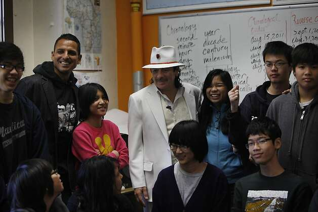 Students in Mr. Aceves' classroom at Mission High school gather with Carlos Santana (center) and Peter Bratt (second from left) for a photograph while Santana toured Mission High school in San Francisco, Calif. on Monday, October 24, 2011. Photo: Lea Suzuki, The Chronicle