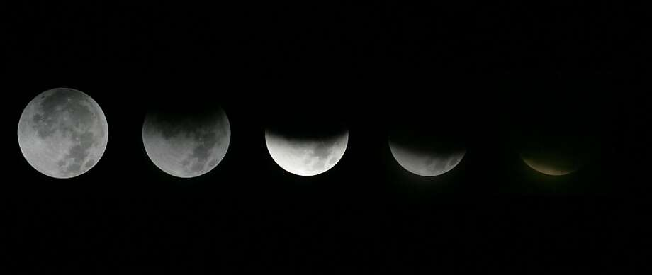 In this photo combination, the different  stages of the moon during a  lunar eclipse as seen from the Griffith Observatory in  in Los Angeles, Saturday, Dec. 10, 2011.  (AP Photo/Ringo H.W. Chiu) Photo: Ringo H.W. Chiu, AP