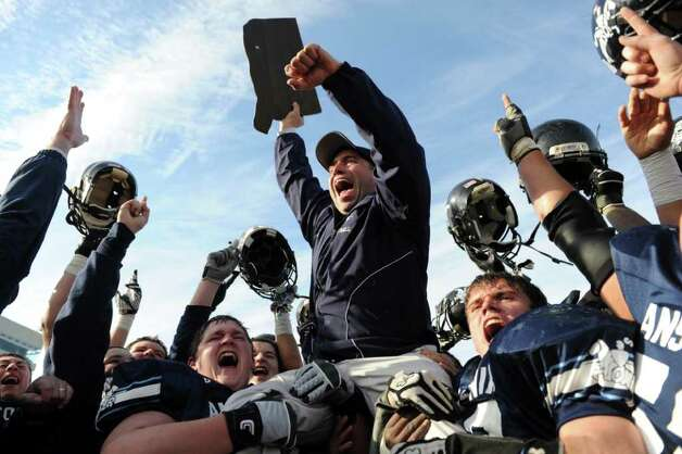 Ansonia lifts up coach Thomas Brockett as they celebrate their win over Ledyard Saturday, Dec. 10, 2011 during the Class M State Championship football game at Rentschler Field in East Hartford, Conn. Photo: Autumn Driscoll / Connecticut Post