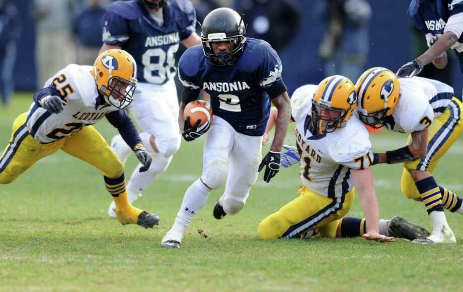 Ansonia's Arkeel Newsome runs the ball through Ledyard's defensive line Saturday, Dec. 10, 2011 during the Class M State Championship football game at Rentschler Field in East Hartford, Conn. Photo: Autumn Driscoll / Connecticut Post