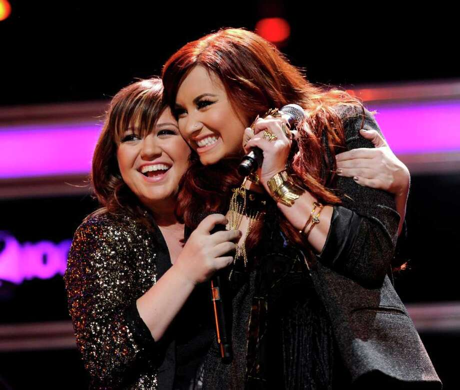 Singers Kelly Clarkson, left, and Demi Lovato perform together at Z100's Jingle Ball concert at Madison Square Garden on Friday, Dec. 9, 2011 in New York. (AP Photo/Evan Agostini) Photo: Evan Agostini