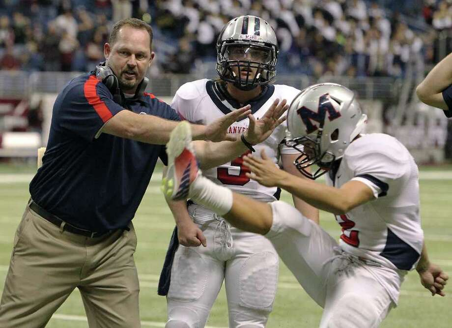 Manvel head coach Kirk Martin (left) gives last minute advice to players including quarterback Shane McCarley (03) and kicker Josh Martinez (02) before Martinez attempts the winning fieldgoal against CalAllen in Class 4A Div. II state semifinals in football at the Alamodome in San Antonio on Saturday, Dec. 10, 2011. Martinez was successful and Manvel defeated CalAllen, 31-28, to advance to the state finals. Kin Man Hui/San Antonio Express-News/kmhui@express-news.net Photo: KIN MAN HUI, SAN ANTONIO EXPRESS-NEWS / SAN ANTONIO EXPRESS-NEWS
