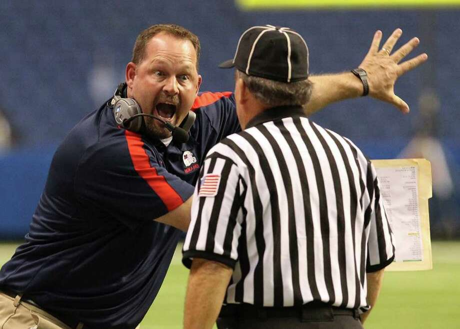 Manvel head coach Kirk Martin (left) tries to convince a game official of a penalty after a play in the first half against CalAllen in Class 4A Div. II state semifinals in football at the Alamodome in San Antonio on Saturday, Dec. 10, 2011. Manvel defeated CalAllen, 31-28, to advance to the state finals. Kin Man Hui/San Antonio Express-News/kmhui@express-news.net Photo: KIN MAN HUI, SAN ANTONIO EXPRESS-NEWS / SAN ANTONIO EXPRESS-NEWS