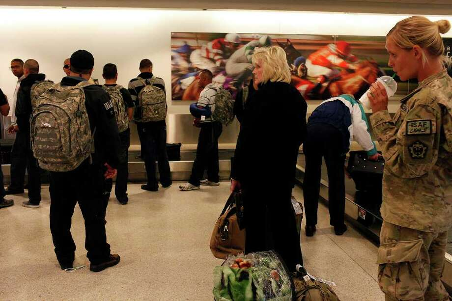 metro - Soldiers and civilians wait for their luggage upon arrival at Louisville International Airport on Saturday, Dec. 3, 2011. The soldiers, stationed in Puerto Rico, came to Louisville for training at Ft. Knox.  Photo: LISA KRANTZ, SAN ANTONIO EXPRESS-NEWS / SAN ANTONIO EXPRESS-NEWS