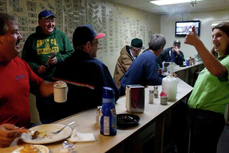 "metro - Kentucky Headhunters restaurant owner, Darlene Curry, right, laughs with customers Dennis ""Buck"" Jagger, from left, Jerry Powell and Oz Coffey as they have breakfast before sunrise in Greensburg, KY on Tuesday, Dec. 6, 2011. The restaurant is written about in a song by the band Kentucky Headhunters called ""Dumas Walker"" which refers to the restaurant's featured meal of ""slaw burger, fries and a bottle of ski."" The restaurant is also called Adolphus Ennis, the name of it's former owner.  Photo: LISA KRANTZ, SAN ANTONIO EXPRESS-NEWS / SAN ANTONIO EXPRESS-NEWS"