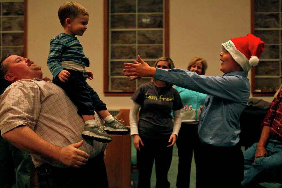 "Will Bonta, 7, right, holds out his arms as the Pastor's son, River Jessie, 20 months, slides down the stomach of Bobby Marcum, left, after they watched the Christmas Play, ""Christmas Hangup,"" at Greensburg Baptist Church in Greensburg, KY on Sunday, Dec. 4, 2011. Bonta's parents both taught Dakota Meyer at Green County High School, where he played football and graduated from. Marcum's wife is the current principal at the high school.  Photo: LISA KRANTZ, SAN ANTONIO EXPRESS-NEWS / SAN ANTONIO EXPRESS-NEWS"