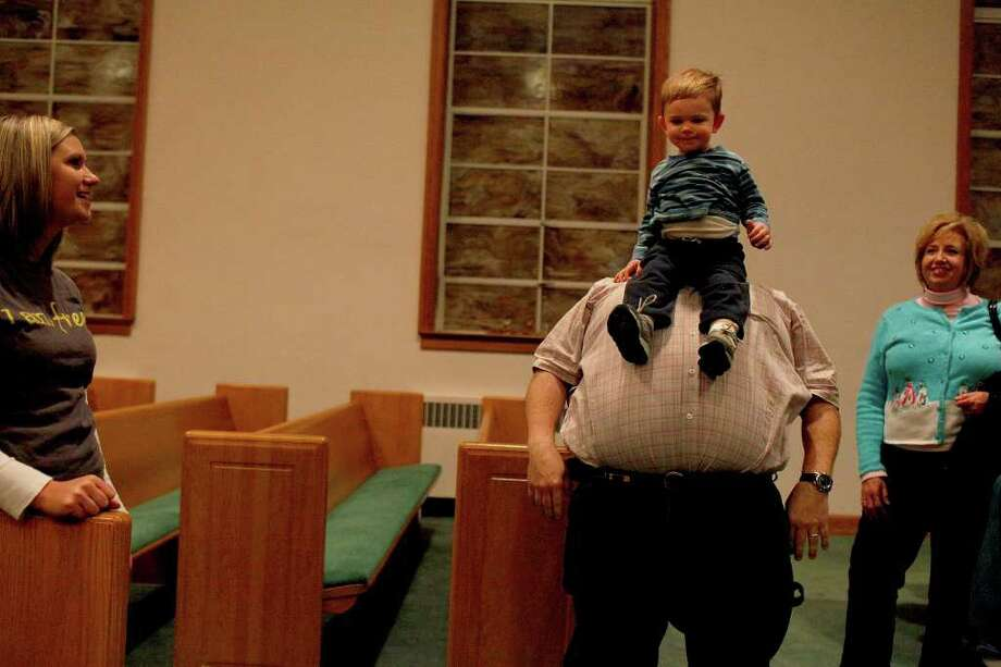 "The Pastor's son, River Jessie, 20 months, slides down the stomach of Bobby Marcum, right, after they watched the Christmas Play, ""Christmas Hangup,"" at Greensburg Baptist Church in Greensburg, KY on Sunday, Dec. 4, 2011. Marcum's wife is the principal at Green County High School, where Dakota Meyer played football and graduated from. Watching are River's mom, Emily Jessie, left, and Patty Durrett, right. Photo: LISA KRANTZ, SAN ANTONIO EXPRESS-NEWS / SAN ANTONIO EXPRESS-NEWS"
