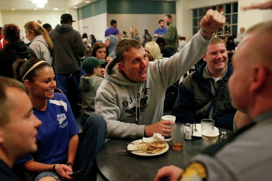 "Dakota Meyer, center, goes for a fist bump with a friend during the ""Midnight Breakfast,"" a tradition for the start of finals week at Lindsey Wilson College, where Meyer has an office, many mentors and will be receiving an Honorary Doctorate Degree this week on Tuesday, Dec. 6, 2011. Meyer is surrounded by his half-brother, Timothy Gilliam, 19, from lett, Myer's girlfriend, Sara Sells, a House Manager at the college, Mike Staten, Director of Public Safety at the College and Kentucky State Trooper Andy Olson.  Photo: LISA KRANTZ, SAN ANTONIO EXPRESS-NEWS / SAN ANTONIO EXPRESS-NEWS"