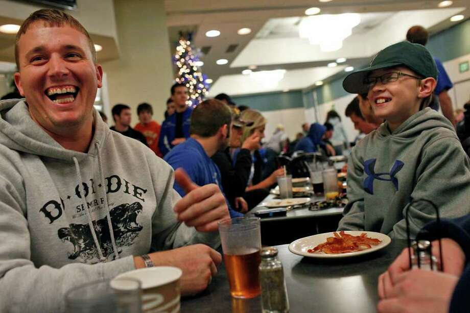"Dakota Meyer laughs with C.J. Bonifer, 11, during the ""Midnight Breakfast,"" a tradition for the start of finals week, at Lindsey Wilson College, where Meyer has an office, many mentors and will be receiving an Honorary Doctorate Degree this week on Tuesday, Dec. 6, 2011.  Photo: LISA KRANTZ, SAN ANTONIO EXPRESS-NEWS / SAN ANTONIO EXPRESS-NEWS"