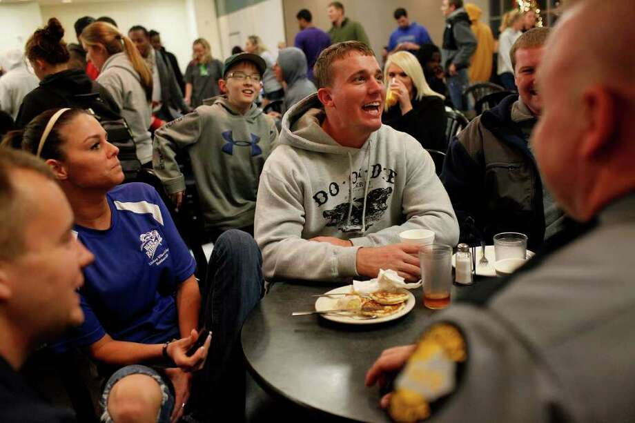 "Dakota Meyer, center, spends time with friends during the ""Midnight Breakfast,"" a tradition for the start of finals week at Lindsey Wilson College, where Meyer has an office, many mentors and will be receiving an Honorary Doctorate Degree this week on Tuesday, Dec. 6, 2011. Meyer is surrounded by his half-brother, Timothy Gilliam, 19, from lett, Myer's girlfriend, Sara Sells, a House Manager at the college, C. J. Bonifer, 11, Mike Staten, Director of Public Safety at the College and Kentucky State Trooper Andy Olson. Photo: LISA KRANTZ, SAN ANTONIO EXPRESS-NEWS / SAN ANTONIO EXPRESS-NEWS"