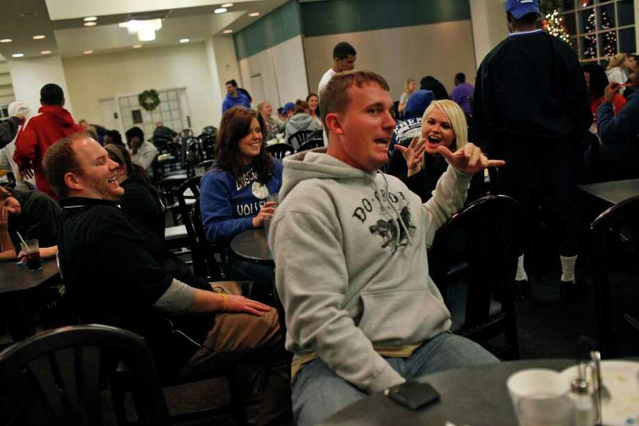 "Dakota Meyer, center, jokes Jordan Willis, from left, Brittany Taylor and Paige Hutchison during the ""Midnight Breakfast,"" a tradition for the start of finals week at Lindsey Wilson College, where Meyer has an office, many mentors and will be receiving an Honorary Doctorate Degree on Saturday, early on Wednesday, Dec. 7, 2011.  Photo: LISA KRANTZ, SAN ANTONIO EXPRESS-NEWS / SAN ANTONIO EXPRESS-NEWS"