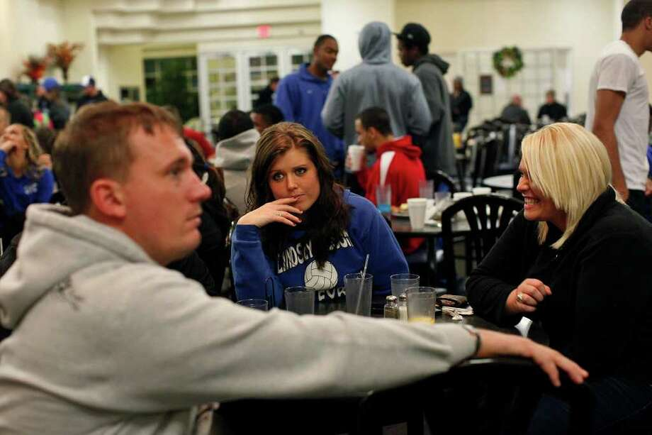 "Brittany Taylor, center, watches Dakota Meyer, left, as she and student Paige Hutchison, talk with him during the ""Midnight Breakfast,"" a tradition for the start of finals week, at Lindsey Wilson College, where Meyer has an office, many mentors and will be receiving an Honorary Doctorate Degree on Saturday, early on Wednesday, Dec. 7, 2011. Photo: LISA KRANTZ, SAN ANTONIO EXPRESS-NEWS / SAN ANTONIO EXPRESS-NEWS"