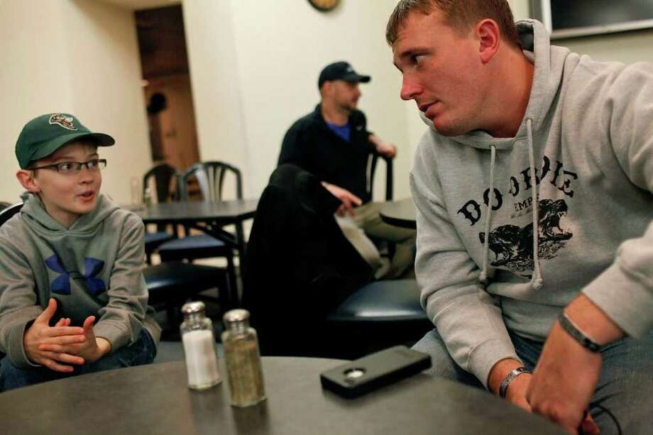 """Dakota Meyer listens to C.J. Bonifer, 11, talk about his relationship history, including many relationship status changes on Facebook, during the """"Midnight Breakfast,"""" a tradition for the start of finals week, at Lindsey Wilson College, where Meyer has an office, many mentors and will be receiving an Honorary Doctorate Degree on Saturday, early on Wednesday, Dec. 7, 2011.  Photo: LISA KRANTZ, SAN ANTONIO EXPRESS-NEWS / SAN ANTONIO EXPRESS-NEWS"""