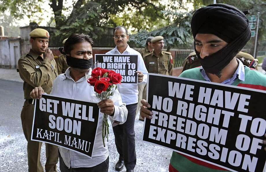 Indian protestors hold placards and flowers outside the residence of India's telecommunications minister Kapil Sibal as they protest against the government plans to screen websites for derogatory content in New Delhi, India, Wednesday, Dec. 7, 2011. Sibal said Tuesday that Internet giants such as Facebook and Google have ignored his demands to screen derogatory material from their sites, so the government would have to act on its own. (AP Photo) Photo: AP
