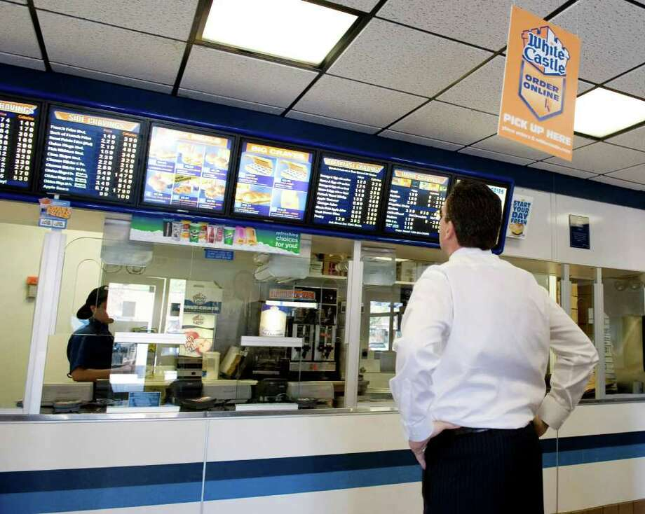 Gov. Dan Malloy checks out the menu at White Castle in the Bronx. Malloy and his staff stopped for lunch on their way to back to Hartford from Ground Zero in New York City on May 5, 2011. White Castle was a favorite stop for Malloy when he was returning from Rugby matches at Randalls Island. Photo: Kathleen O'Rourke / Stamford Advocate
