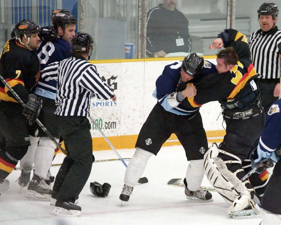 New England Stars goalie Peter Maro, right, fights with a member of the Danville Pounders during an Eastern Professional Hockey League game at the Danbury Arena in 2007. Maro, a 46-year-old orthodontist, made is debut with the Danbury Whalers last Sunday. At left is the Stars' Phil Esposito, who is now the Whalers head coach. Photo: Contributed Photo