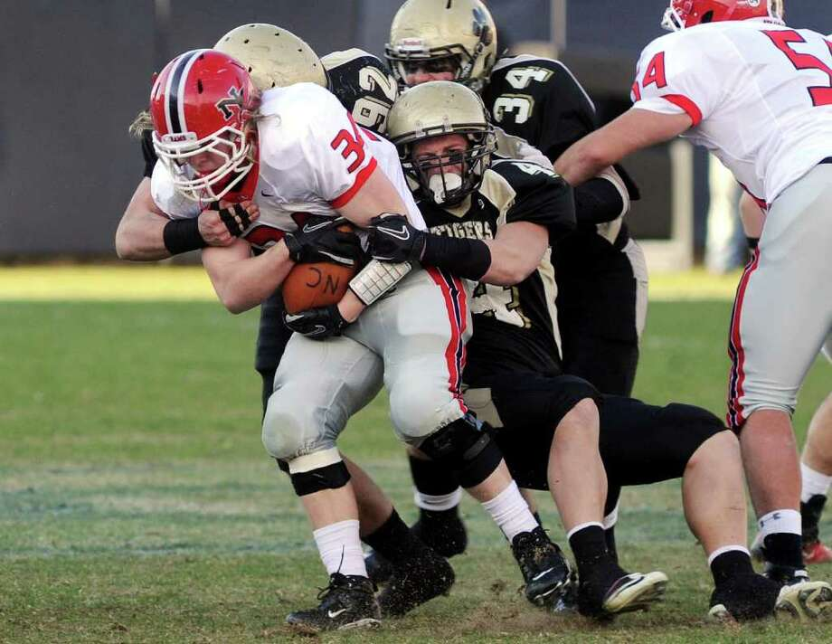 Highlights from CIAC Class L boys football championship action between New Canaan and Daniel Hand in East Haven, Conn. on Saturday December 10, 2011. New Canaan's #34 Robert Distler gets pulls down by a Hand player. Photo: Christian Abraham / www.connpost.com