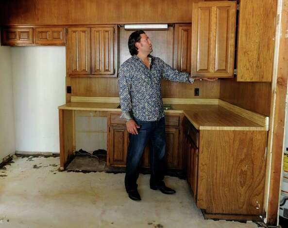 In this file photo, Armando Montelongo examines kitchen cabinets as he tours a home in San Antonio. Photo: BILLY CALZADA, SAN ANTONIO EXPRESS-NEWS / gcalzada@express-news.net