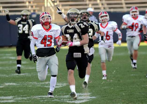 Daniel Hand's #24 Kevin Frey outruns several New Canaan players to take the ball into the endzone for the team's first touchdown, during CIAC Class L boys football championship action in East Hartford, Conn. on Saturday December 3, 2011. Photo: Christian Abraham / www.connpost.com