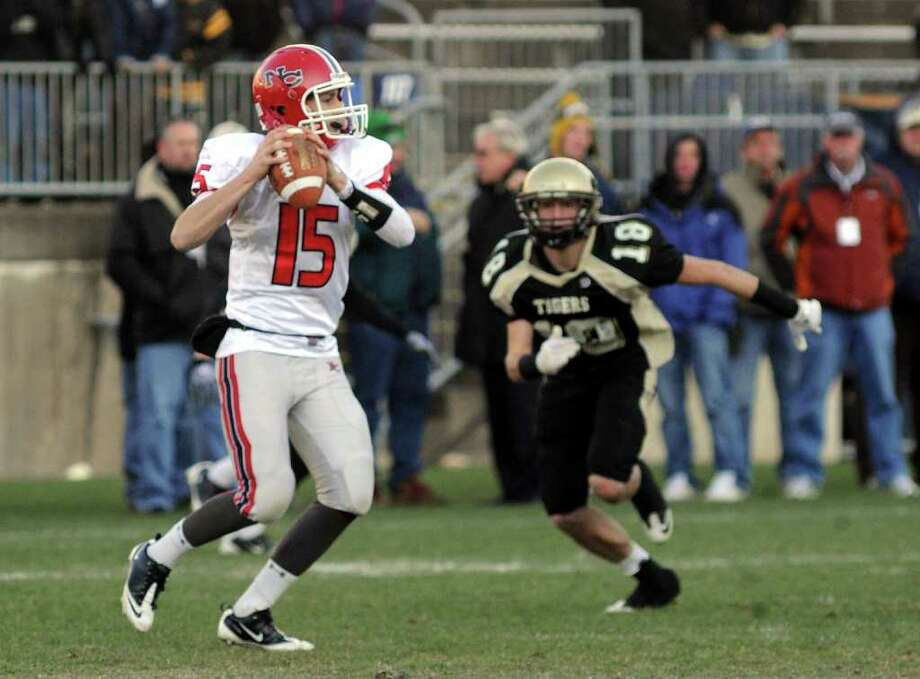 Highlights from CIAC Class L boys football championship action between New Canaan and Daniel Hand in East Haven, Conn. on Saturday December 10, 2011. New Canaan QB #15 Matthew Milano prepares to pass as Hand's #18 Andrew Federico looks to sack. Photo: Christian Abraham / www.connpost.com