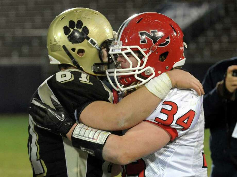 Highlights from CIAC Class L boys football championship action between New Canaan and Daniel Hand in East Haven, Conn. on Saturday December 10, 2011. Hand's #61 Mitchell Pasqualoni, left, and New Canaan's #34 Robert Distler embrace after New Canaan was defeated by hand 34-10. Photo: Christian Abraham / www.connpost.com