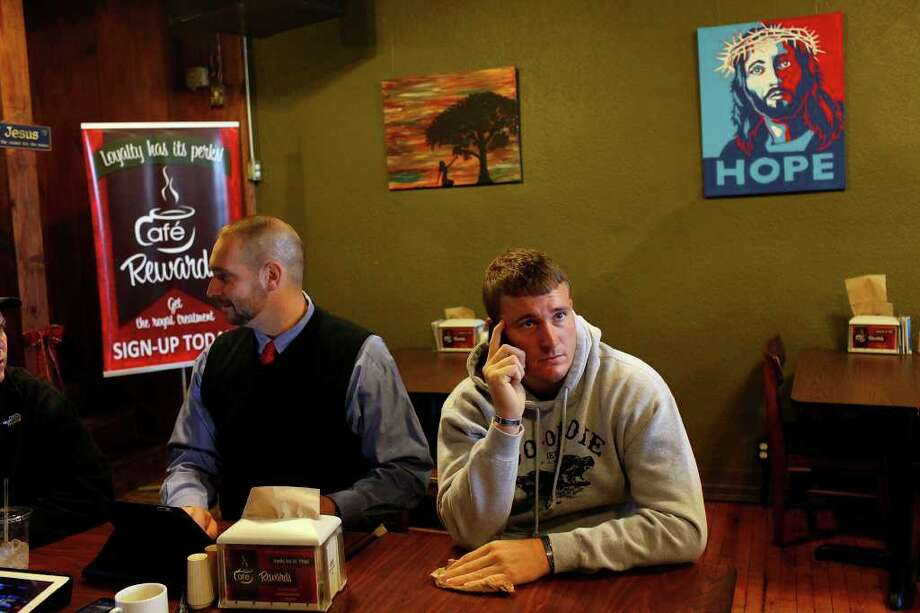 Dakota Meyer talks on the phone next to Chris Schmidt, Dean of Students at Lindsey Wilson College and a mentor to Meyer, at Cafe on the Square in Columbia, KY on Friday, Dec. 9, 2011. The men, with other mentors, try to meet every Friday morning but talk every day.  Photo: LISA KRANTZ, SAN ANTONIO EXPRESS-NEWS / SAN ANTONIO EXPRESS-NEWS