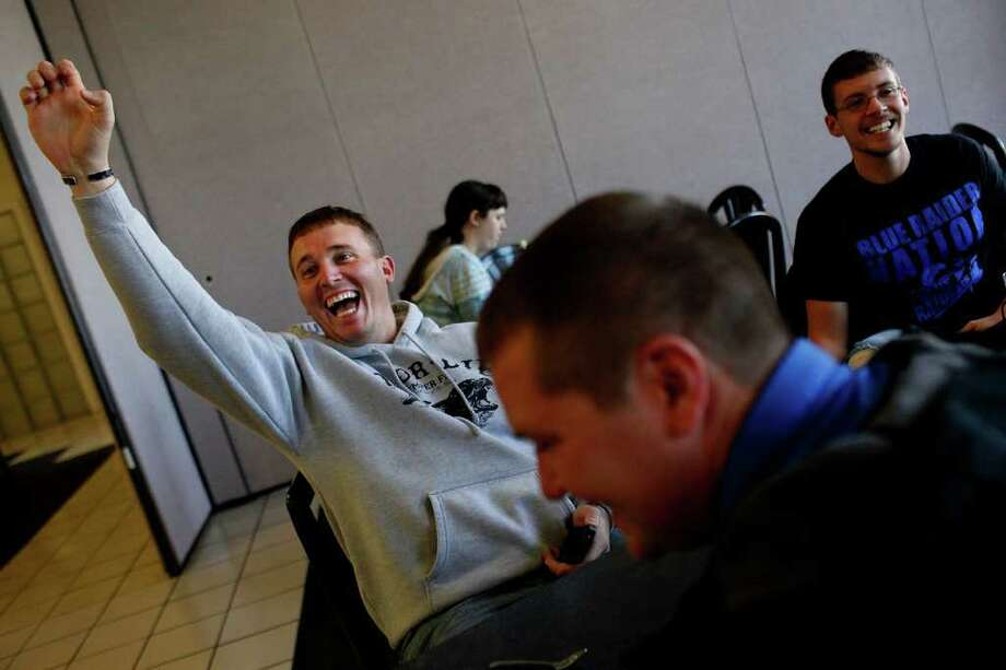 Dakota Meyer (left) waves to a friend arriving for lunch in the dining hall at Lindsey Wilson College, where Meyer has an office, in Columbia, Ky. Photo: LISA KRANTZ, SAN ANTONIO EXPRESS-NEWS / SAN ANTONIO EXPRESS-NEWS