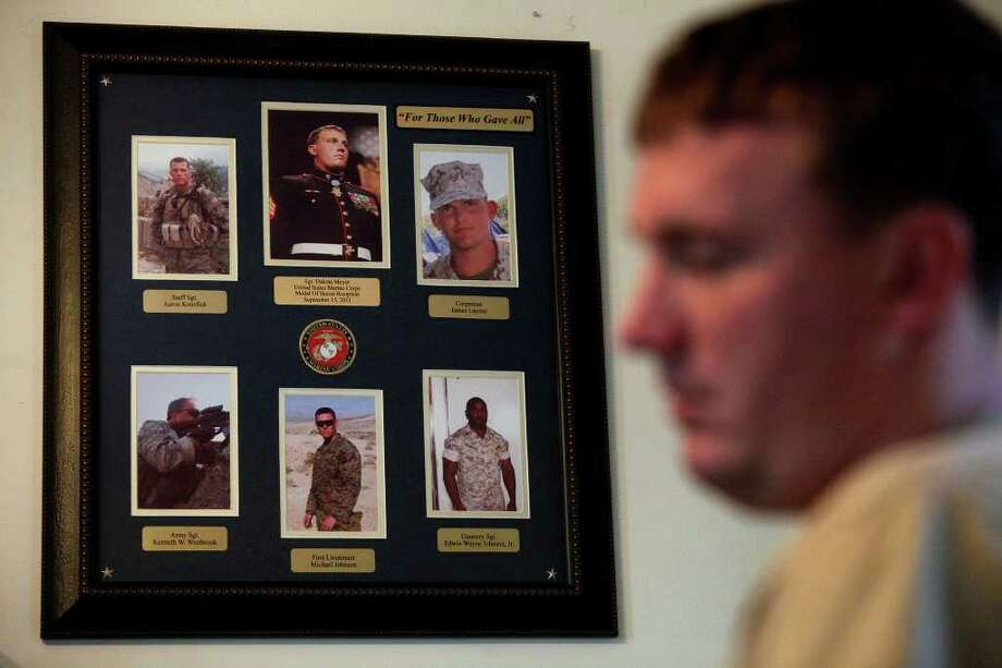 Photos of the four men in his unit who were killed in the Battle of Ganjgal, Afghanistan, and another solider who was injured in the battle and died a month later from his wounds, hangs in Dakota Meyer's office at Lindsey Wilson College in Columbia, KY on Friday, Dec. 9, 2011. Meyer was awarded the Medal of Honor for his actions during the battle, saving the lives of 36 men. Photo: LISA KRANTZ, SAN ANTONIO EXPRESS-NEWS / SAN ANTONIO EXPRESS-NEWS