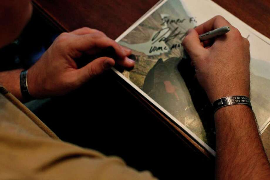 """I have four names on my wrists that hold me accountable every single day,"" Dakota Meyer says of the two bracelets he wears memorializing the four men in his unit who were killed in the Battle of Ganjgal, Afghanistan, as he works in his office at Lindsey Wilson College in Columbia, KY on Friday, Dec. 9, 2011.  Photo: LISA KRANTZ, SAN ANTONIO EXPRESS-NEWS / SAN ANTONIO EXPRESS-NEWS"