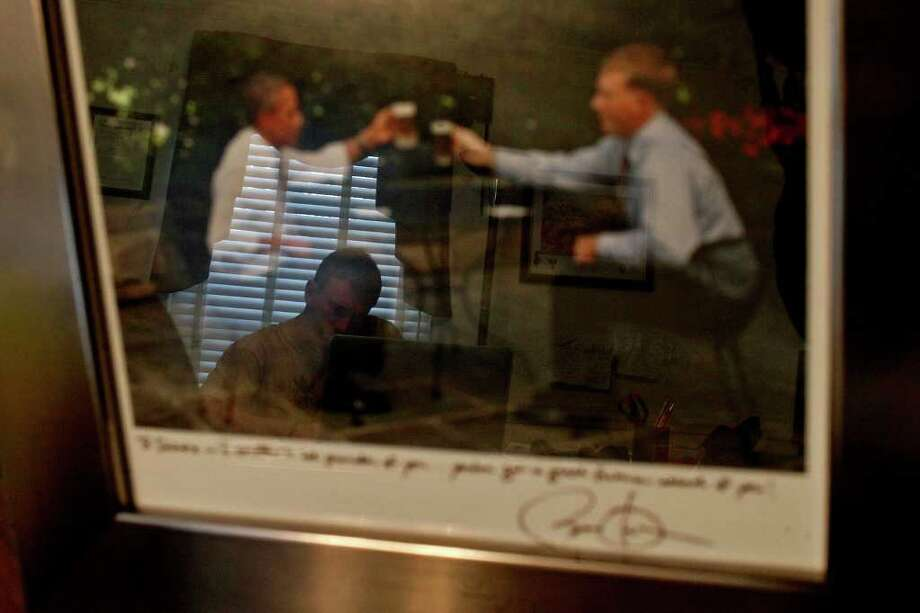 Reflected in the signed photograph of himself sharing a beer with President Barack Obama, Dakota Meyer works in his office at Lindsey Wilson College in Columbia, KY on Friday, Dec. 9, 2011.  Photo: LISA KRANTZ, SAN ANTONIO EXPRESS-NEWS / SAN ANTONIO EXPRESS-NEWS