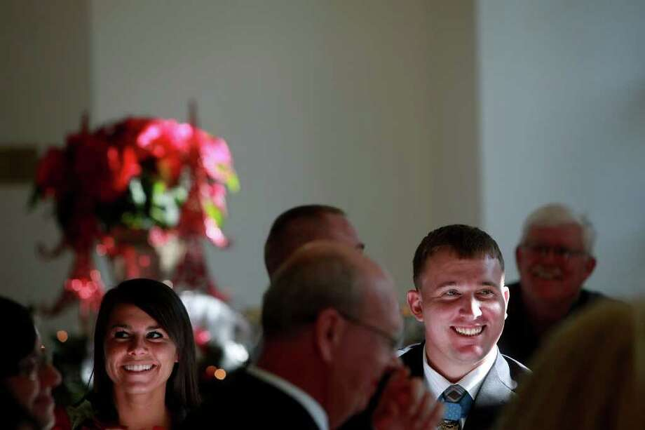 Medal of Honor recipient Dakota Meyer laughs with his girlfriend, Sara Sells, left, as he is spoken about during a luncheon after the Lindsey Wilson College Commencement where he received an Honorary Doctorate Degree in Columbia, KY on Saturday, Dec. 10, 2011.  Photo: LISA KRANTZ, SAN ANTONIO EXPRESS-NEWS / SAN ANTONIO EXPRESS-NEWS