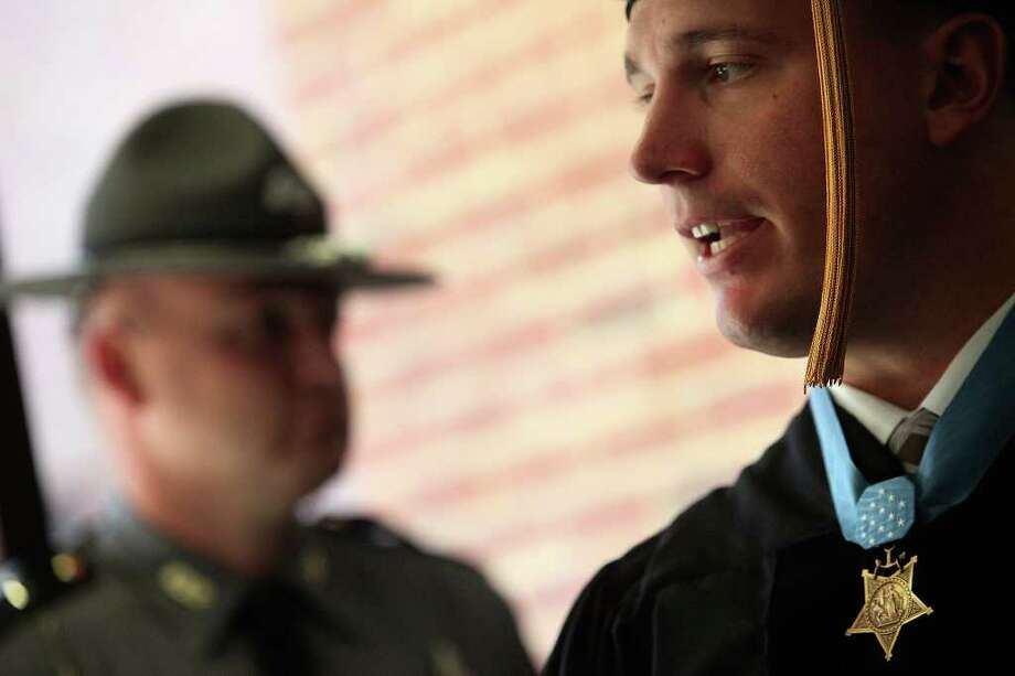 Dakota Meyer is watched over by Kentucky State Police Trooper Andy Olson, left, as Meyer talks with faculty members before the Lindsey Wilson College Commencement where he received an Honorary Doctorate Degree in Columbia, KY, where he was born and grew up, on Saturday, Dec. 10, 2011. Photo: LISA KRANTZ, SAN ANTONIO EXPRESS-NEWS / SAN ANTONIO EXPRESS-NEWS