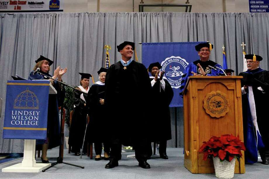 Dakota Meyer receives a standing ovation as he receives an Honorary Doctorate Degree during the Lindsey Wilson College Commencement presented by the college President, Dr. William T. Luckey, Jr., right, in the college's gymnasium in Columbia, KY on Saturday, Dec. 10, 2011.  Photo: LISA KRANTZ, SAN ANTONIO EXPRESS-NEWS / SAN ANTONIO EXPRESS-NEWS