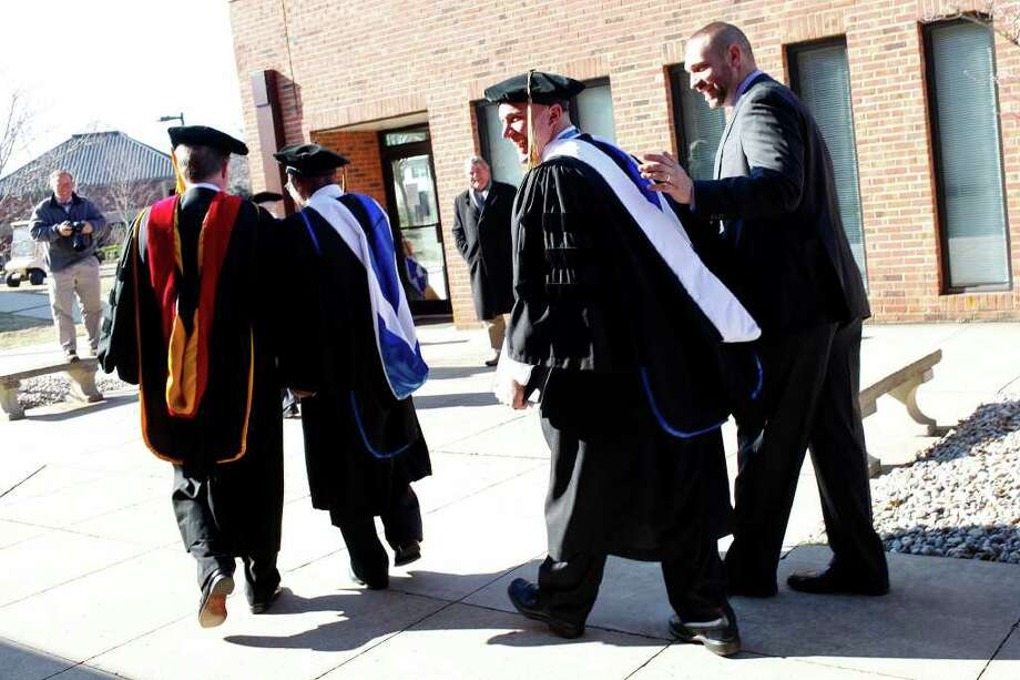 Chris Schmidt, right, the Dean of Students and mentor to Dakota Meyer, center, congratulates Meyer after he received an Honorary Doctorate Degree during the Lindsey Wilson College Commencement in Columbia, KY, where he was born and grew up, on Saturday, Dec. 10, 2011.  Photo: LISA KRANTZ, SAN ANTONIO EXPRESS-NEWS / SAN ANTONIO EXPRESS-NEWS