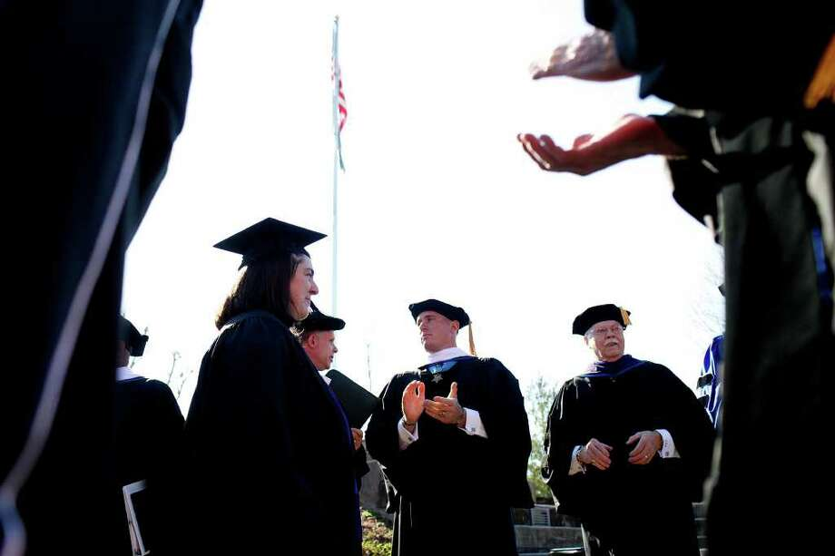 Dakota Meyer, center, applauds graduates after the Lindsey Wilson College Commencement where he received an Honorary Doctorate Degree from the college in Columbia, KY, where he was born and grew up, on Saturday, Dec. 10, 2011.  Photo: LISA KRANTZ, SAN ANTONIO EXPRESS-NEWS / SAN ANTONIO EXPRESS-NEWS