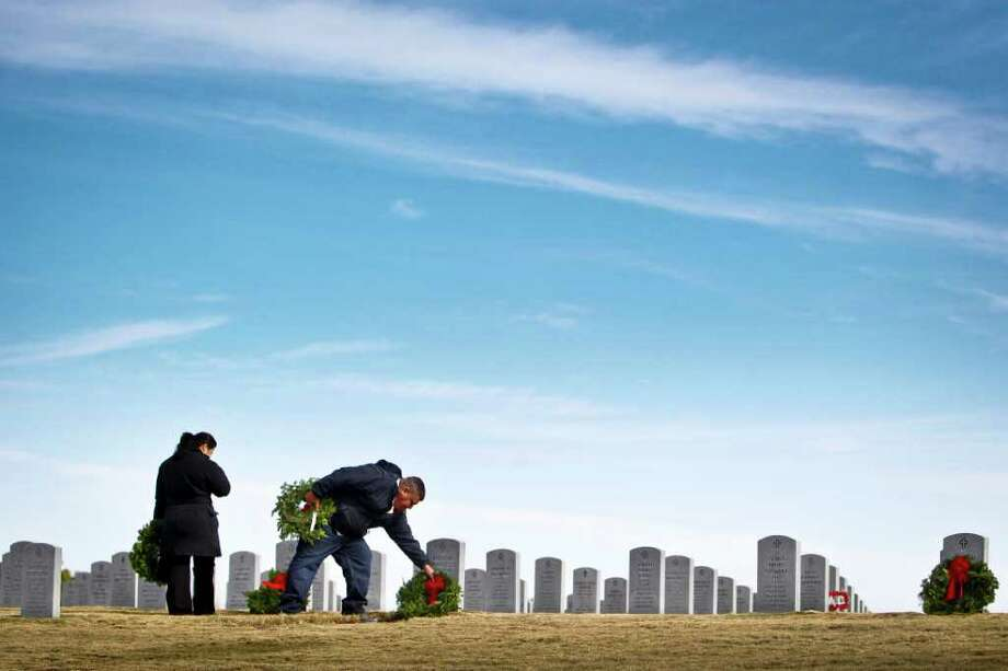Ray Rodriguez places a commemorative wreath on a grave as his wife Rachael looks on during the Wreaths Across America-Houston campaign at the Houston VA National Cemetery, Saturday, Dec. 10, 2011, in Houston. Photo: Michael Paulsen, Houston Chronicle / © 2011 Houston Chronicle