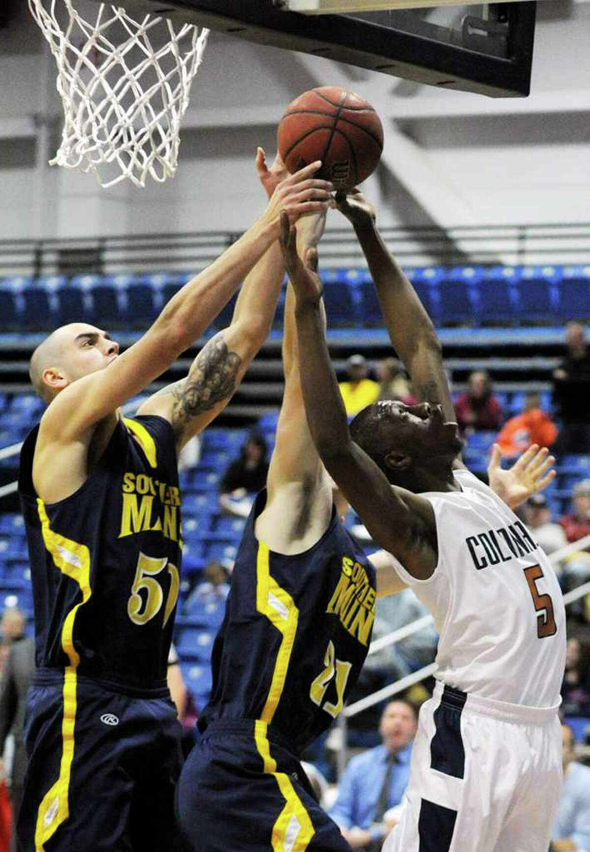 University of Southern Maine's John Roberts, left, and Alex Kee compete with Western Connecticut State University's Ter'Quwan Perkins for the rebound during their game at the O'Neill Center on WestConn's Westside campus on Saturday, Dec. 10, 2011. WestConn won 88-58.