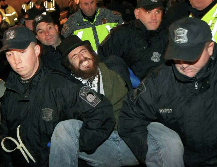 Boston police officers remove an Occupy Boston protester from Dewey Square in Boston before dawn Saturday, Dec. 10, 2011. More than 40 people were peacefully arrested as the park was cleared. The city had set a Thursday midnight deadline for protesters to leave or face eviction.  (AP Photo/The Boston Globe, Essdras M Suarez, , Pool) Photo: Essdras M Suarez