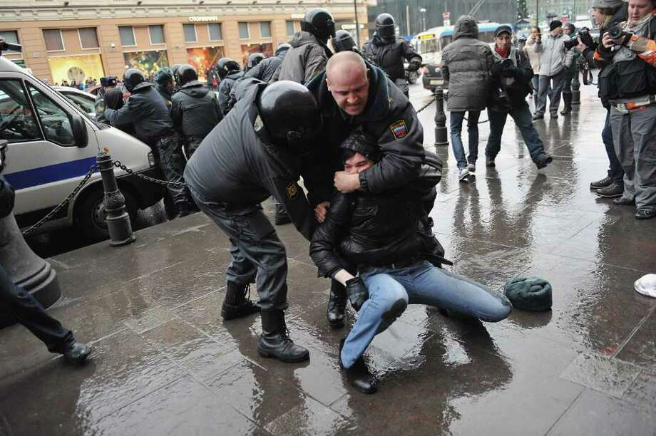 Police officers detain an opposition activist outside the area of an authorized opposition protest against the alleging mass fraud in the December 4 parliamentary polls in central St.Petersburg, on December 10, 2011. Tens of thousands of election protesters turned out today in Moscow and other major cities across Russia in open defiance to strongman Vladimir Putin's 12-year rule. Photo: OLGA MALTSEVA, Getty / AFP