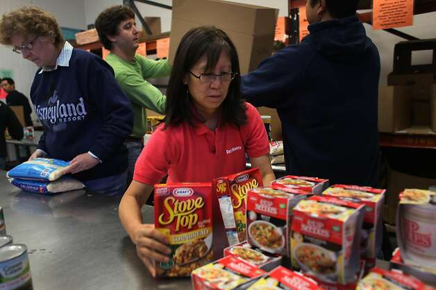 Sorting through food donations, Frances Jin joins a group of volunteers from Del Monte Foods at the Food Bank of Contra Costa and Solano Counties, on Friday Dec. 2, 2011 in Concord, Calif. Season of Sharing donates 15% of its funds directly to food banks. Over the past 25 years food banks have received 12 million dollars from SOS. Photo: Mike Kepka, The Chronicle