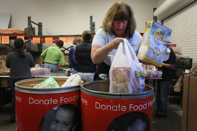Sorting through food donations, Janine Peery joins a group of volunteers from DelMonte Foods at the Food Bank of Contra Costa and Solano Counties, on Friday Dec. 2, 2011 in Concord, Calif. Season of Sharing donates 15% of its funds directly to food banks. Over the past 25 years food banks have received 12 million dollars from SOS. Photo: Mike Kepka, The Chronicle