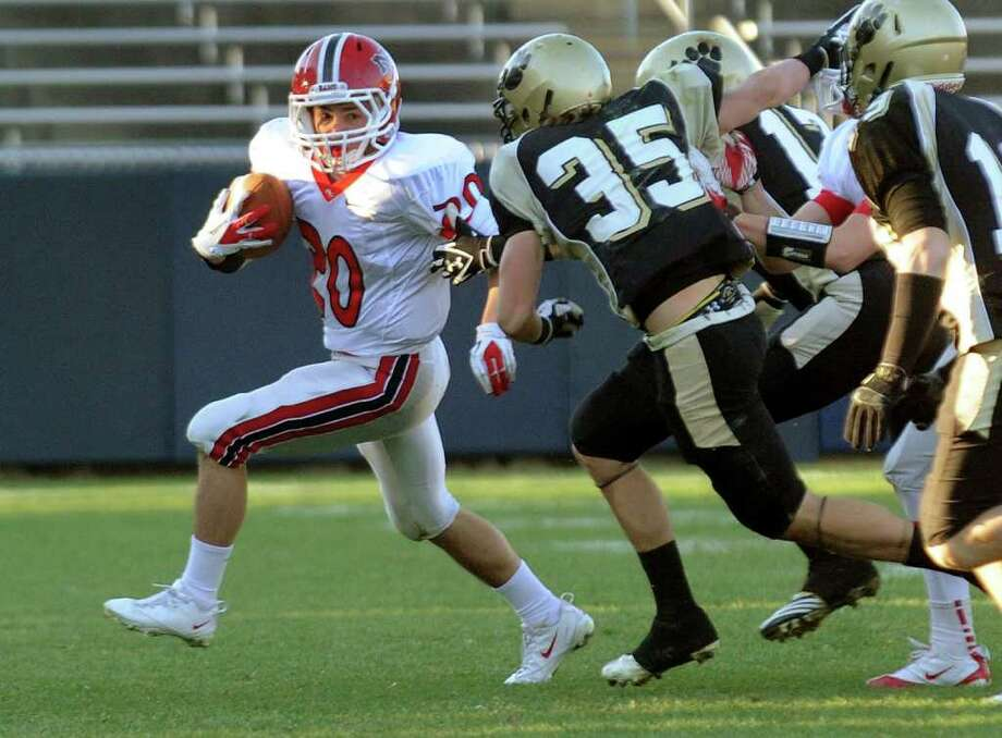 Highlights from CIAC Class L boys football championship action between New Canaan and Daniel Hand in East Haven, Conn. on Saturday December 10, 2011. New Canaan's #20 Mike Bossidy looks to evade Hand's #35 Alexander Tuccero. Photo: Christian Abraham / www.connpost.com