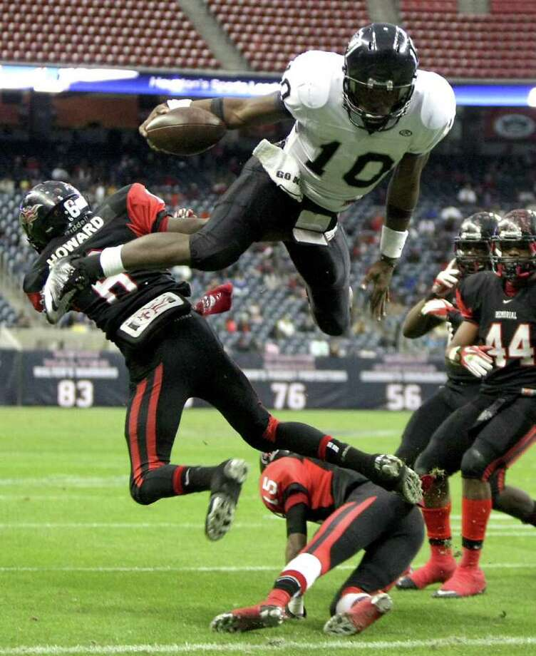 Cibolo Steele High School quarterback Tommy Armstrong jumps over Port Arthur Memorial High School's Jaylon Howard for his second touchdown during the second quarter of a Class 5-A Division II semifinal high school football game, Saturday, Dec. 10, 2011, in Reliant Stadium in Houston. Photo: Nick De La Torre, Houston Chronicle / © 2011  Houston Chronicle